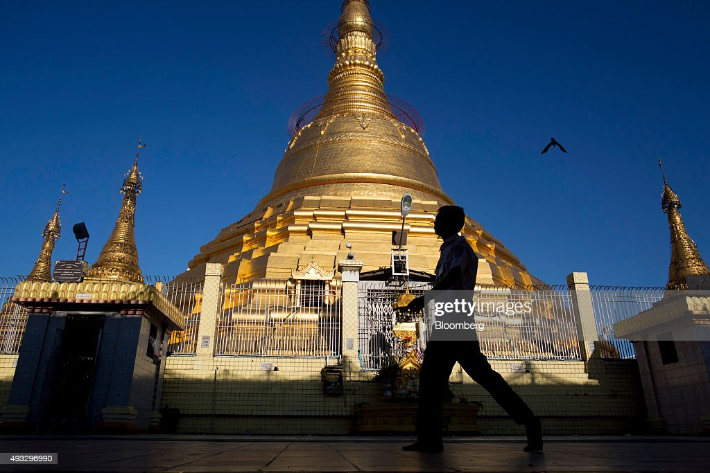 A pedestrian is silhouetted as he walks past the Botataung Pagoda in Yangon, Myanmar, on Thursday, Oct. 15, 2015. Myanmar's government signed a cease-fire agreement with half of the nation's armed ethnic groups, a partial victory for President Thein Sein less than a month before an historic national election. Photographer: Brent Lewin/Bloomberg via Getty Images