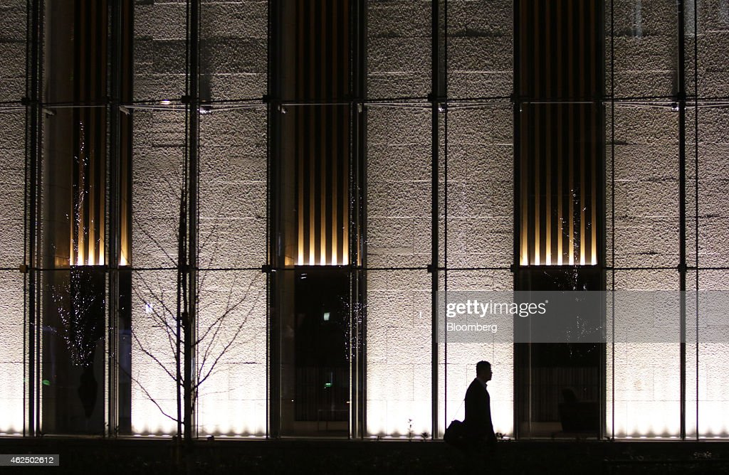 A pedestrian is silhouetted as he walks past the Mizuho Financial Group Inc. headquarters in Tokyo, Japan, on Thursday, Jan. 29, 2015. Mizuho Financial Group, Japan's third largest bank, is scheduled to report third-quarter earnings on Jan. 30. Photographer: Tomohiro Ohsumi/Bloomberg via Getty Images