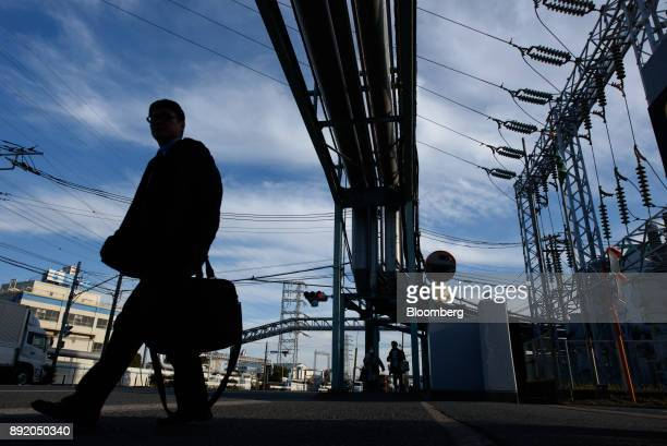 A pedestrian is silhouetted as he walks under a pipeline in the Keihin industrial area of Kawasaki Kanagawa Prefecture Japan on Tuesday Dec 12 2017...