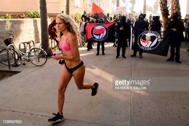 """Pedestrian jogs past counter-protesters, some carrying ANTIFA flags, as they wait to confront a """"Patriot March"""" demonstration in support of US..."""