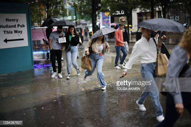 Pedestrian jumps a puddle as they cross the road during heavy rain in central London on July 28, 2021.