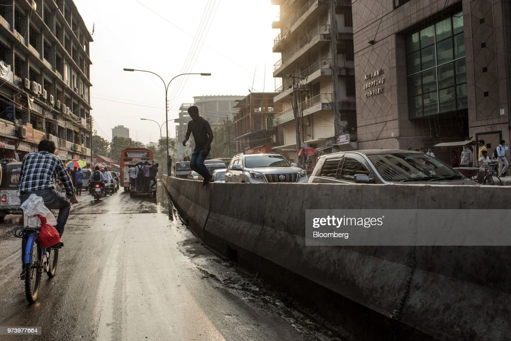 A pedestrian jumps from the central reservation while crossing a road in the Gulshan area of Dhaka, Bangladesh, on Wednesday, June 6, 2018. The Bangladesh economy will expand 6.9% this financial year and 6.8% in 2019, according to asurveyconducted by Bloomberg News. Photographer: Ismail Ferdous/Bloomberg via Getty Images
