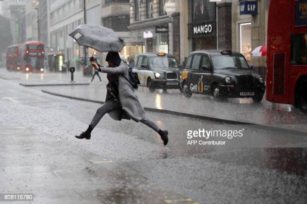 A pedestrian leaps over a puddle as rain fell in central London on August 9 2017 / AFP PHOTO / Tolga AKMEN