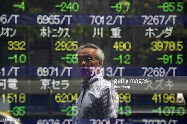 A pedestrian looking at figures is reflected in an electronic board outside a securities firm in Tokyo Japan on Friday Aug 21 2015Japanese stocks...