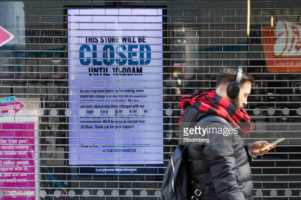 A pedestrian looking at his mobile phone passes a sign informing customers of a late opening on an electronic screen in the shuttered window of a...