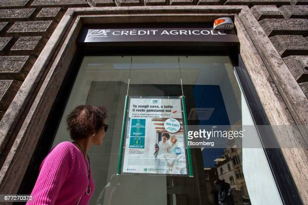 Pedestrian looks an advertising displayed inside the window of a branch of Credit Agricole SA's Cariparma bank in Rome, Italy, on Tuesday, May 2,...