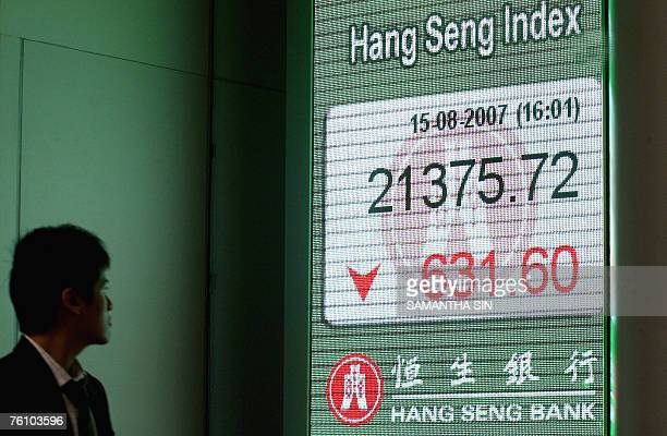 Pedestrian looks at a digital screen showing the decline in Hong Kong's Heng Seng Index, 15 August 2007. Hong Kong share prices closed sharply lower,...