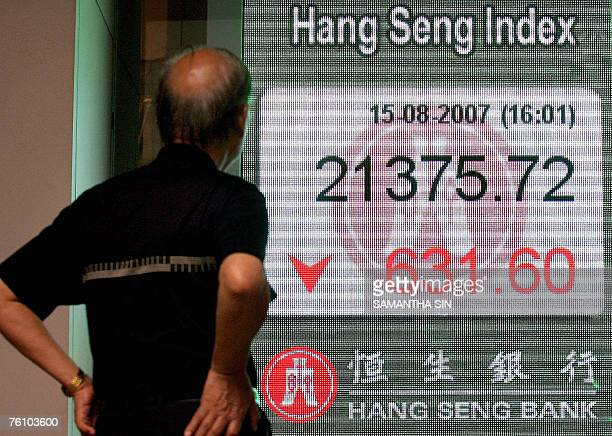 A pedestrian looks at a digital screen showing the decline in Hong Kong's Heng Seng Index 15 August 2007 Hong Kong share prices closed sharply lower...