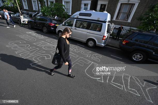 A pedestrian looks at a message chalked onto the road outside the home of Number 10 Downing Street special advisor Dominic Cummings in London on May...