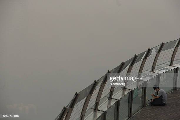 Pedestrian looks at a smart device from a viewing point in the Marina Bay district as buildings in the central business area stand shrouded in smog...