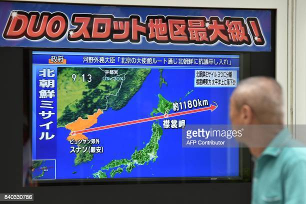 A pedestrian looks at a television screen displaying a map of Japan and the Korean Peninsula in Tokyo on August 29 following a North Korean missile...