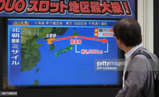 A pedestrian looks at a television screen displaying a map of Japan and the Korean Peninsula in Tokyo on September 15 following a North Korean...