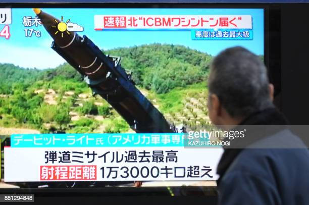 A pedestrian looks at a television screen displaying file news footage of a missile launch in Tokyo on November 29 2017 Japan's prime minister said...