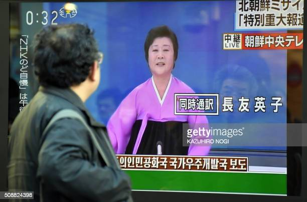 A pedestrian looks at a television screen showing the Korean Central Television special broadcast on North Korea's rocket launch in Tokyo on February...