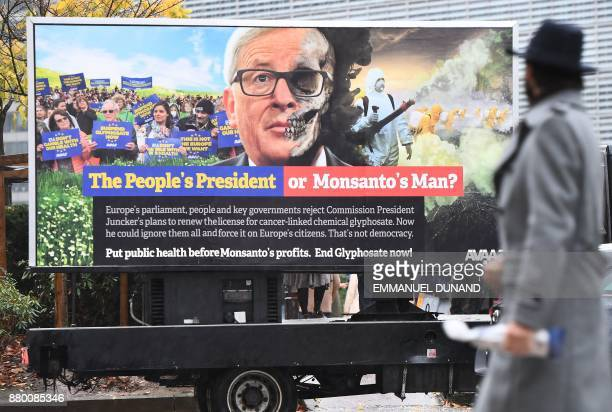 A pedestrian looks at a truck displaying a billboard featuring European Commission President JeanClaude Juncker during an action calling for the EU...