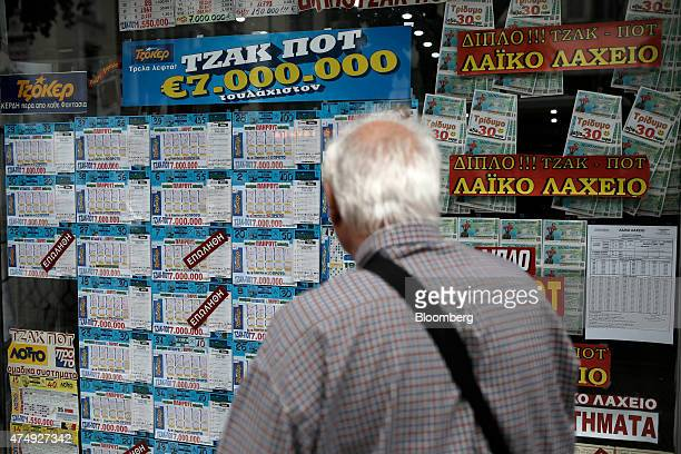 A pedestrian looks at an advertisement for a seven million euro lottery prize draw in the window of a store in Thessaloniki Greece on Thursday May 28...