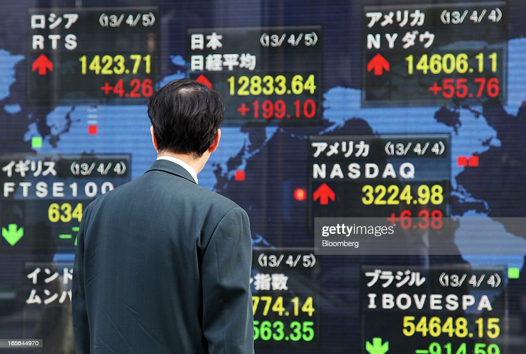 A pedestrian looks at an electronic stock board outside a securities firm in Tokyo, Japan, on Friday, April 5, 2013. Japanese stocks surged, with the Nikkei 225 Stock Average capping the biggest three-day rally in two years, after Haruhiko Kuroda announced unprecedented stimulus in his first policy meeting as Bank of Japan governor. Photographer: Junko Kimura/Bloomberg via Getty Images