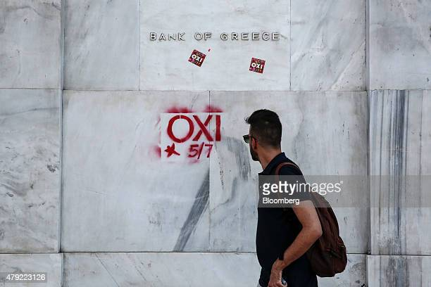 A pedestrian looks at antiausterity graffiti reading 'OXI' or 'NO' sprayed onto the wall of the headquarters of Greece's central bank in Athens...