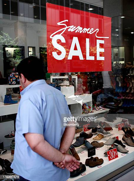 A pedestrian looks at men's shoes in the window of a store advertising a summer sale in Athens Greece on Friday Aug 9 2013 Greece's economy...