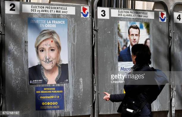 A pedestrian looks at official campaign posters of Marine Le Pen French National Front and political party leader and an official poster of Emmanuel...