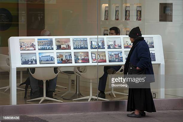 A pedestrian looks at properties displayed for sale in the window of a Foxtons estate agents store in the Brixton district of London UK on Monday May...
