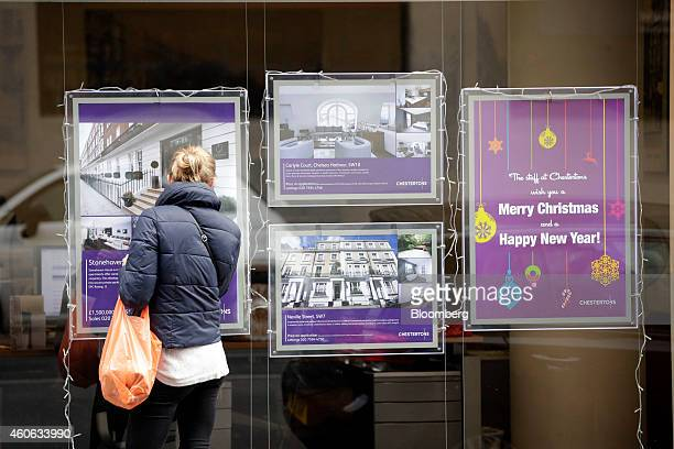 A pedestrian looks at property information leaflets for luxury homes displayed in the window of an estate agent in the Chelsea district of London UK...