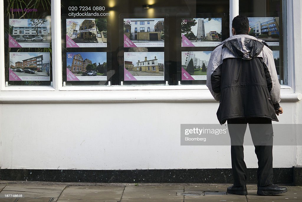 A pedestrian looks at residential properties displayed for sale in the window of an estate agents in London, U.K., on Tuesday, Nov. 12, 2013. Under Bank of England Governor Mark Carney's forward-guidance policy, the central bank has pledged to not to withdraw stimulus at least until unemployment falls to 7 percent. Photographer: Simon Dawson/Bloomberg via Getty Images