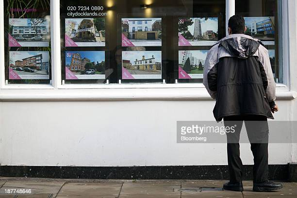 A pedestrian looks at residential properties displayed for sale in the window of an estate agents in London UK on Tuesday Nov 12 2013 Under Bank of...