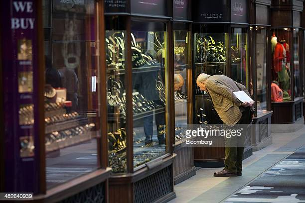 A pedestrian looks at rings and watches displayed in the window of a jewelry store in the Burlington Arcade in London UK on Thursday April 3 2014...
