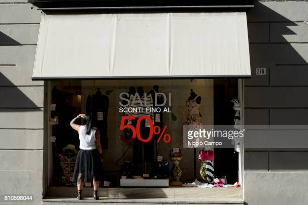 A pedestrian looks at shop window with a writing announcing the sales during the Italian summer sales