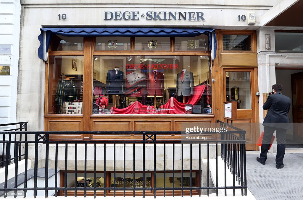 A pedestrian looks at the window display of the tailors Dege & Skinner based on Savile Row in London, U.K., on Tuesday, July 2, 2013. New orders at manufacturers rose for a fourth month in June, led by the textiles clothing industry, while input costs fell for a third month. Photographer: Chris Ratcliffe/Bloomberg via Getty Images