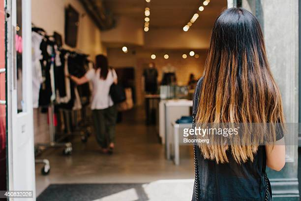 A pedestrian looks into the doorway of a shop in the SoHo neighborhood of New York US on Wednesday June 18 2014 The Bloomberg Consumer Comfort Index...