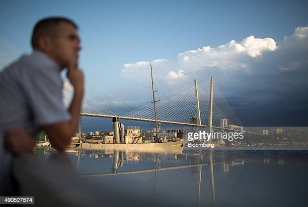 A pedestrian looks out towards the memorial ship 'Red Pennant' also known as 'Krasnyy Vympel' near Golden bridge on Golden Horn Bay in Vladivostok...