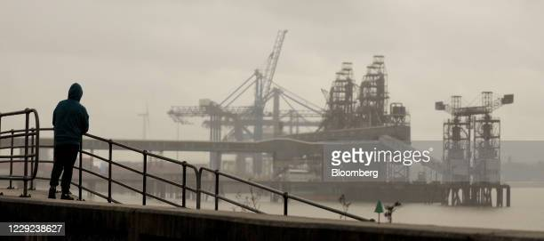 Pedestrian looks out towards the Port of Tilbury London Ltd., operated by Forth Ports Ltd., in London, U.K., on Friday, Oct. 23, 2020. Global trade...
