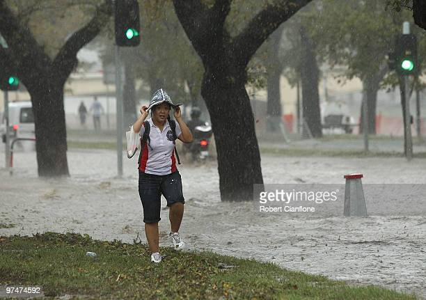Pedestrian looks to get out of heavy rain as Batman Avenue is flooded as massive storms hit Melbourne city on March 6, 2010 in Melbourne, Australia....