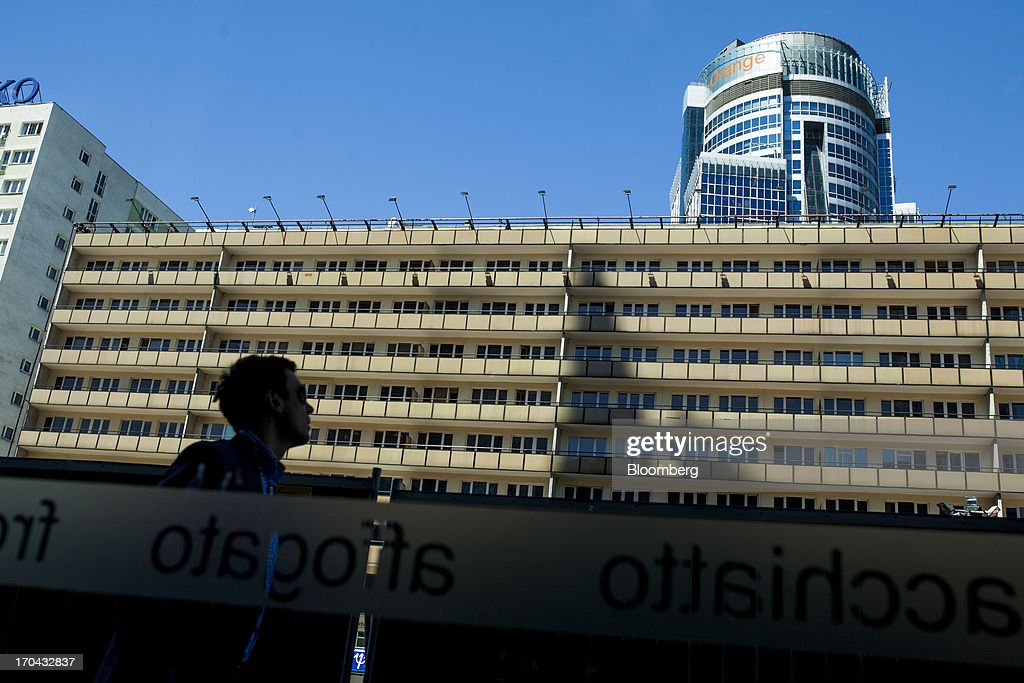 A pedestrian looks up towards the headquarters of Orange Polska, right, also known as Telekomunikacja Polska SA (TPSA), Poland's national telecommunications company, in Warsaw, Poland, on Wednesday, June 12, 2013. Cable providers are being drawn to Poland, the European Union's biggest eastern economy, because penetration levels are half that of neighboring Germany even as unemployment rises, according to a website presentation by the country's biggest TV network, Cyfrowy Polsat SA. Photographer: Bartek Sadowski/Bloomberg via Getty Images