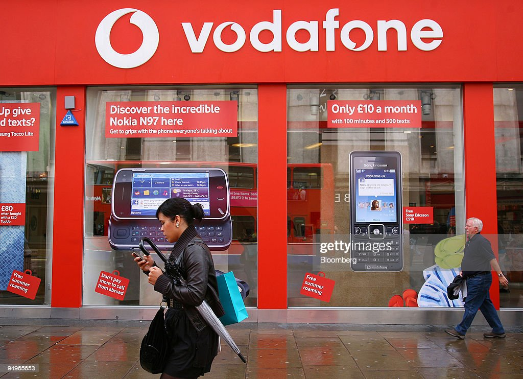 A pedestrian makes a call on her mobile phone outside the Vo : News Photo