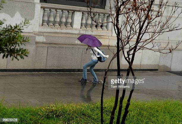 A pedestrian makes her way through a puddle near Capitol City Brewery
