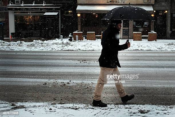 A pedestrian navigates the snow ice and puddles along a Manhattan street on February 2 2015 in New York City Another winter storm has brought...