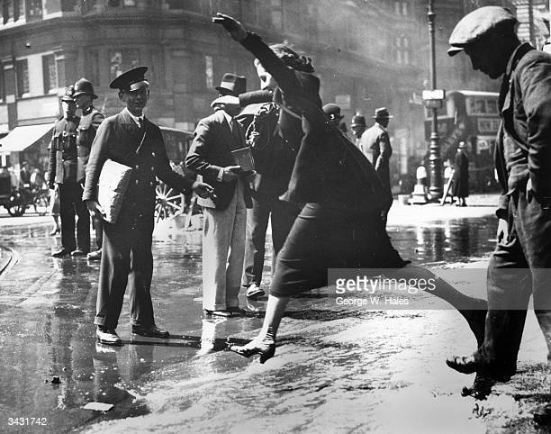 A pedestrian negotiating a burst water main in Theobald's Road Bloomsbury London 16th June 1936