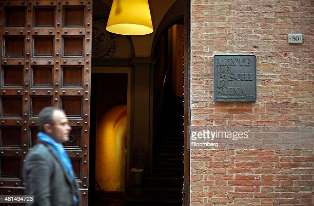 A pedestrian passes a Banca Monte dei Paschi di Siena SpA bank branch in Siena Italy on Wednesday Jan 8 2014 Monte Paschi the bailed out Italian bank...