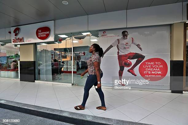 A pedestrian passes a Bharti Airtel Ltd mobile phone store at the Spar shopping mall in Port Harcourt Nigeria on Tuesday Jan 12 2016 With his...