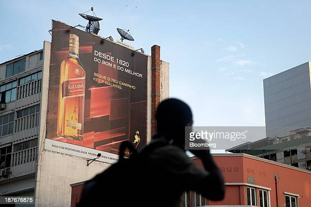 A pedestrian passes a billboard advertising Johnnie Walker 'Red Label' whisky in Luanda Angola on Saturday Nov 9 2013 Angola the largest crude oil...