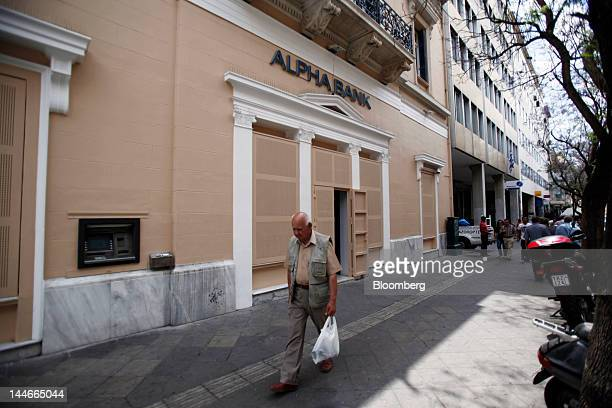 A pedestrian passes a branch of Alpha Bank AE protected by security screens in Athens Greece on Thursday May 17 2012 The European Central Bank said...