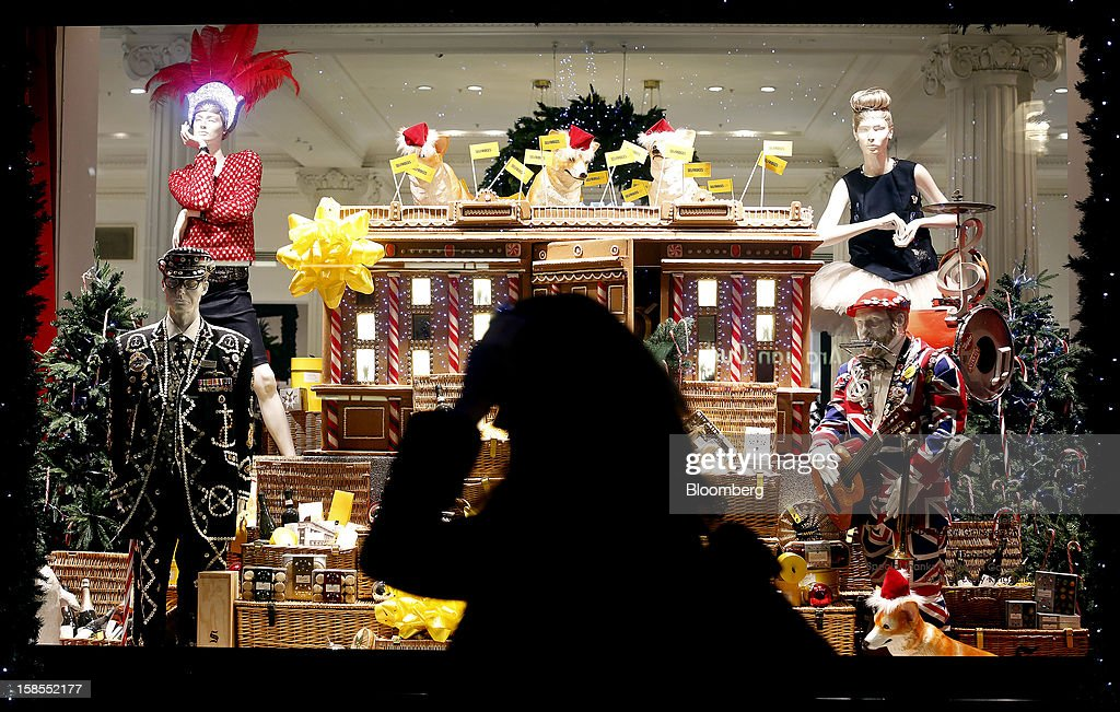 A pedestrian passes a Christmas window display dressed to reflect British culture including a London Pearly King, a one-man band and models of Queen Elizabeth II's corgi dogs at the Selfridges department store, operated by Selfridges Plc, on Oxford Street in London, U.K., on Monday, Dec. 17, 2012. Retailers are relying on Christmas sales to help rescue a year when high unemployment and the debt crisis have blighted spending. Photographer: Simon Dawson/Bloomberg via Getty Images