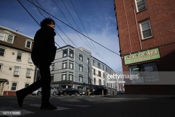 Pedestrian passes a completed luxury condo building on Washington Street in Union Square in Somerville, MA alongside the neighborhood's stock of...