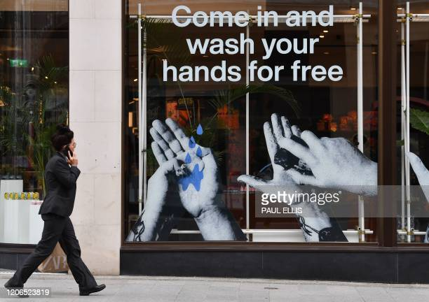 A pedestrian passes a cosmetics shop advertising free hand washing facilities in store in Liverpool northwest England on March 11 2020