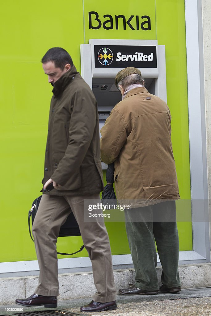 A pedestrian passes a customer using an automated teller machine (ATM) outside a Bankia SA branch in Madrid, Spain, on Thursday, Feb. 28, 2013. BFA-Bankia Chairman Jose Ignacio Goirigolzarri said a balance sheet clean-up that inflicted a 21.2 billion-euro ($27.6 billion) after-tax loss last year will set the Spanish banking group on course to repay state aid. Photographer: Angel Navarrete/Bloomberg via Getty Images