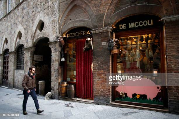 A pedestrian passes a delicatessen store in Siena Italy on Wednesday Jan 8 2014 Banca Monte dei Paschi di Siena SpA the bailed out Italian bank is...