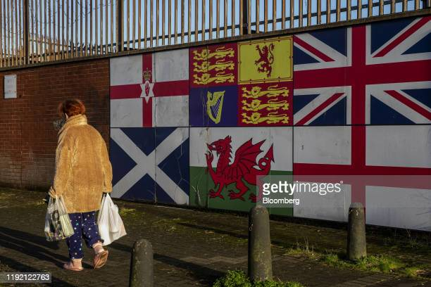 A pedestrian passes a display of national flags clockwise from top left of the Ulster Banner the Royal Standard British Union Flag also known as the...